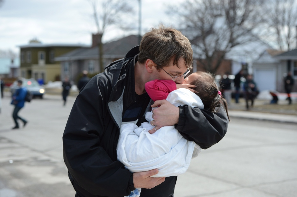 A child is hugged after police release the children to family after a gun incident at a daycare in Gatineau on Friday April 5, 2013. (Sean Kilpatrick / THE CANADIAN PRESS)
