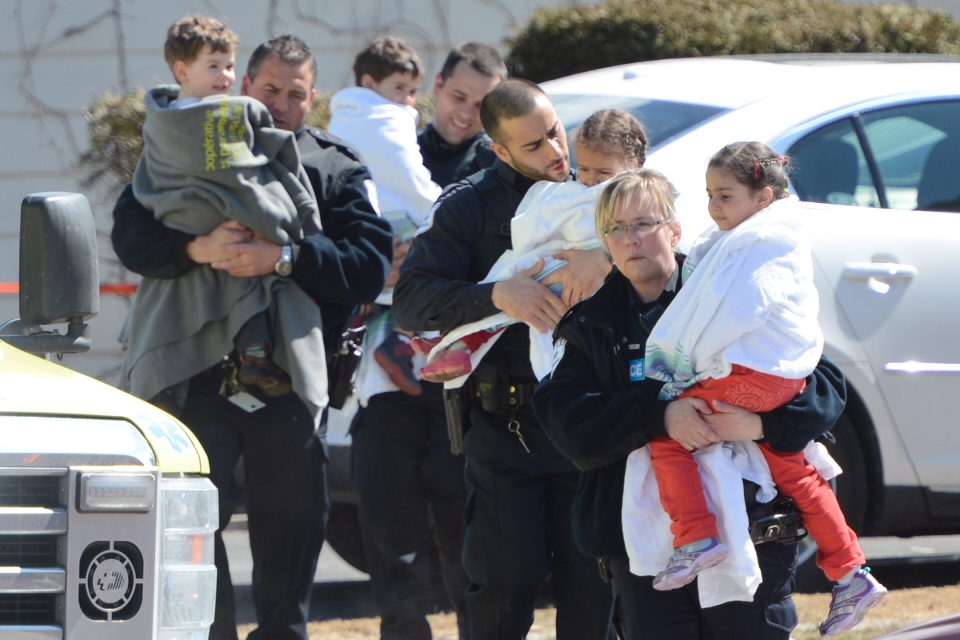 Police carry children from a safehouse to waiting parents and guardians in Gatineau, Que., after a gun incident at a daycare on Friday April 5, 2013. (Sean Kilpatrick / THE CANADIAN PRESS)