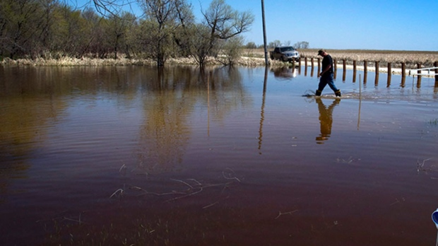 Peter Bradley walkss through the floodwaters in front of his home in Twin Beach, Manitoba, Wednesday, May 18, 2011. (Ryan Remiorz / THE CANADIAN PRESS)