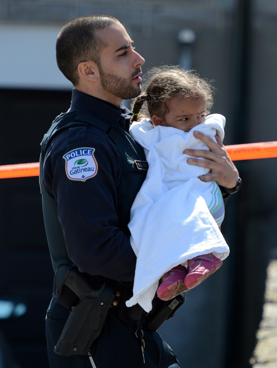 Police carry children from a safehouse to waiting parents and guardians after a shooting at a daycare in Gatineau, Que., on Friday April 5, 2013. (Sean Kilpatrick / THE CANADIAN PRESS)