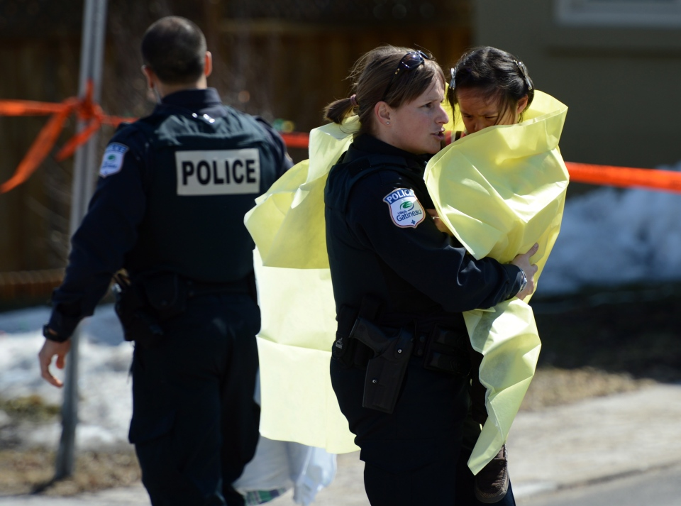 Police carry children from a safehouse to waiting parents and guardians in Gatineau, Que. on Friday April 5, 2013. (Sean Kilpatrick / THE CANADIAN PRESS)