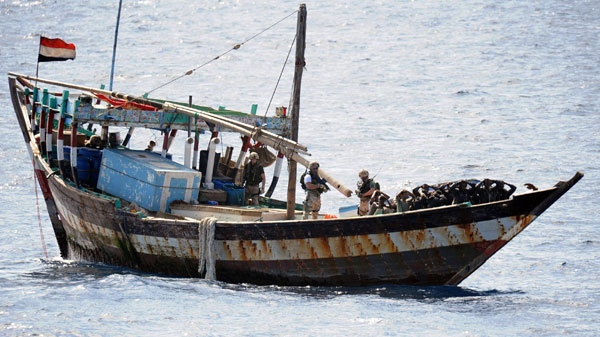 In this image made available by the Ministry of Defence in London, Thursday Feb. 16, 2011, a naval boarding party from HMS Cornwall guard Somali pirates after their dhow was boarded in the Indian Ocean on Thursday Feb. 10, 2011.