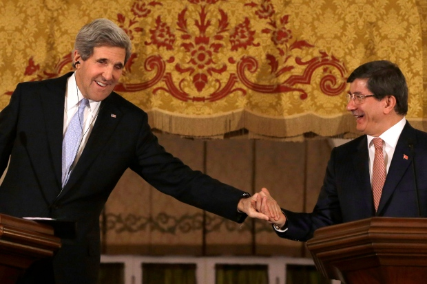 U.S. Secretary of State John Kerry leans over to clasp Turkish Foreign Minister Ahmet Davutoglu's hand at the end of a news conference at Ankara Palace in Ankara, Turkey, on Friday, March 1, 2013. (AP / Jacquelyn Martin)