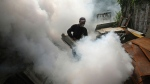 A health ministry worker discharges anti-mosquito spray as a preventive measure to control dengue fever, in Sidoarjo, East Java, Indonesia, in this file photo dated Thursday, March 14, 2013.  (AP / Trisnadi, File)