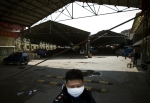 A security guard seen wearing a face mask stands guard at a poultry market which has been closed by local government officials in Nanjing in east China's Jiangsu province on Saturday, April 6, 2013.  (AP)