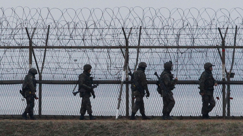 South Korean army soldiers patrol along a barbed-wire fence near the border village of the Panmunjom, in Paju, South Korea, Monday, April 8, 2013. (AP / Ahn Yong-joon)