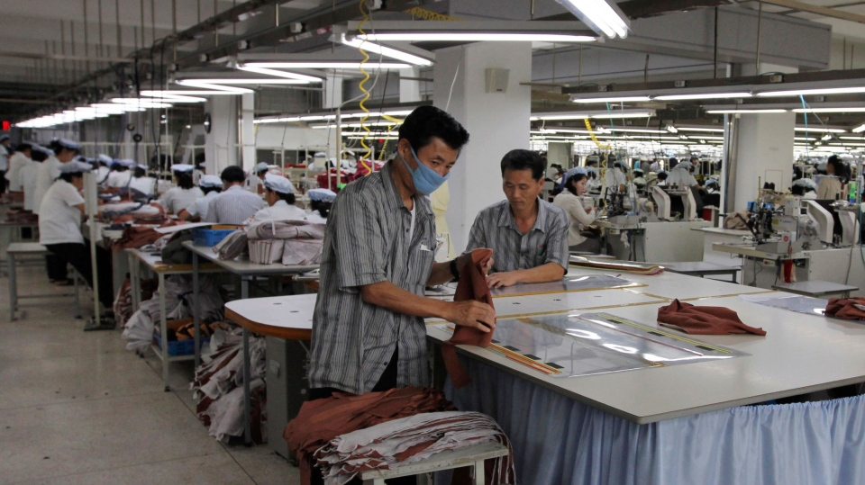 Two North Korean men working for ShinWon, a South Korean clothing maker, prepare garments for production at a factory in Kaesong, North Korea Sept. 21, 2012. (AP / Jean H. Lee)