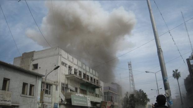 Smoke rises from a bank in Jalalabad, east of Kabul, Afghanistan, Saturday, Feb. 19, 2011. (AP / Shir Shah Hamdard)