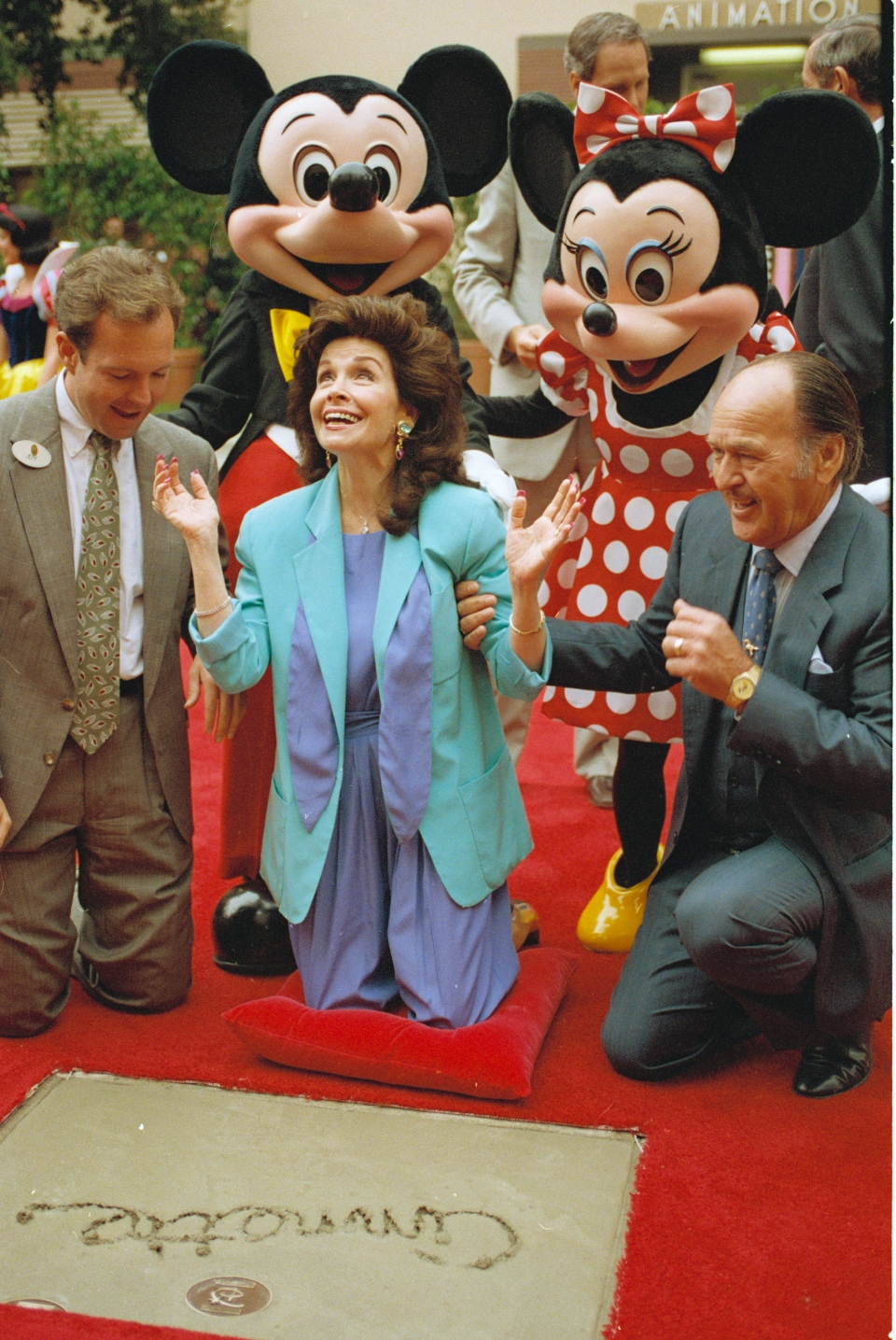"Former ""Mouseketeer"" Annette Funicello gets set to put her hands in the cement at Walt Disney Studios Theatre, as she is honored with the Disney Legend Award in Burbank, Calif., on Oct. 21, 1992. With Funicello is her husband, Glen Holt, right, and Jeff Hofman, left, Disney Studios official.  (AP / Nick Ut)"