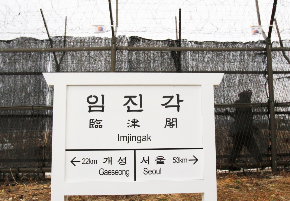 A South Korean army soldier patrols along a barbed-wire fence near a directional sign showing the distance to North Korea's Kaesong city and South Korea's capital Seoul at the Imjingak Pavilion near the border village of the Panmunjom, in Paju, South Korea, Monday, April 8, 2013. (AP / Ahn Yong-joon)
