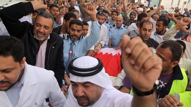Bahraini anti-government protesters chant slogans as they move the body of Redha Buhameed who was killed by the Bahraini Army during a protest on Friday, at a hospital in Manama, Bahrain, Monday, Feb. 21, 2011. (AP / Hasan Jamali)
