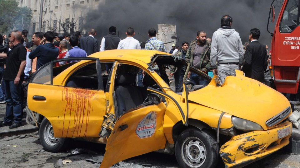 Syrians inspect a damaged car at the scene of a car bomb attack near the Sabaa Bahrat Square, one of the capital's biggest roundabouts, in Damascus, Syria, Monday, April. 8, 2013. (SANA)