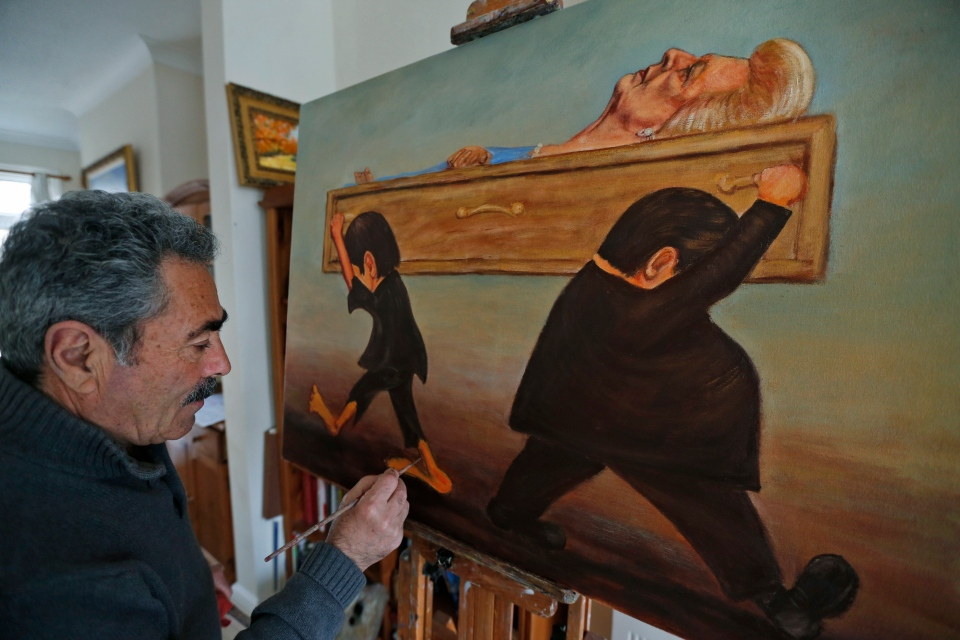 Political painter Kaya Mar, 56, paints the final details of his latest painting depicting the funeral of former British Prime Minister Margaret Thatcher at his home in London, Wednesday, April 10, 2013. (AP / Lefteris Pitarakis)