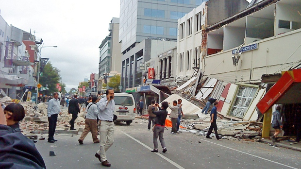 People walk through a street partly covered with rubble after an earthquake hit Christchurch, New Zealand, Tuesday, Feb. 22, 2011. (AP / Xinhua, Pu Rui)