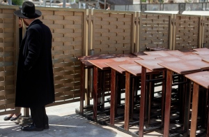 An ultra-Orthodox Jewish man speaks to a woman across a fence separating men and women at the Western Wall, the holiest site where Jews can pray in Jerusalem's old city, Wednesday, April 10, 2013. (AP / Sebastian Scheiner)