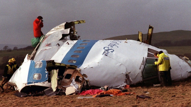Police and investigators look at what remains of the flight deck of Pan Am 103 on a field in Lockerbie, Scotland on Dec. 22, 1988. (AP Photo)