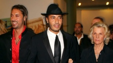 From left, sons of Libyan President Moammar Gadhafi, Mutassim and Saadi, are accompanied by Italian movie producer Marina Cicogna during the 62nd Venice Film Festival at Venice's Lido, northern Italy, Friday, Sept. 9, 2005. (AP / Luigi Costantini)