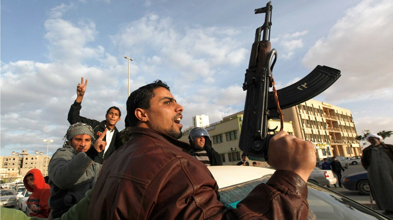 A Libyan protester holds a weapon as he shouts slogans against Libyan Leader Moammar Gadhafi, during a demonstration in Tobruk, Libya, Wednesday, Feb. 23, 2011. (AP / Hussein Malla)