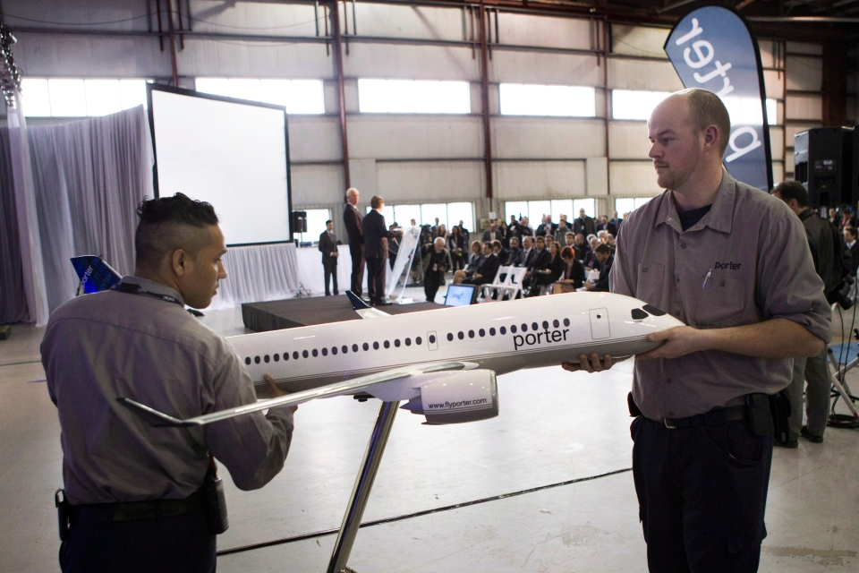 Employees position a model CS100 Aircraft as Bob Deluce, President and CEO of Porter Airlines and the company's Chairman Don Carty take question from the media after he announces the Airlines purchase of 12 of the planes, with an option for a further 18, at a news conference in Toronto on Wednesday April 10, 2013. (Chris Young / THE CANADIAN PRESS)