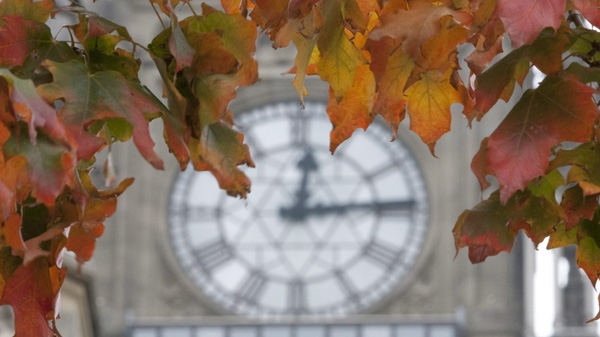 In this Sept. 24, 2010 file photo, changing autumn leaves frame the clock on the Peace Tower on Parliament Hill in Ottawa. (THE CANADIAN PRESS/Adrian Wyld)