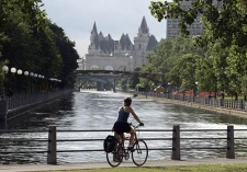 A cyclist pedals along side the Rideau Canal in Ottawa, Mon. June 19, 2006, with the historic Chateau Laurier in the background, where the Rideau Canal flows into the Ottawa River. Ontario's Rideau Canal system, a 202-kilometre long historic waterway, is vying for recognition as a UNESCO World Heritage Site. (CP / Fred Chartrand)