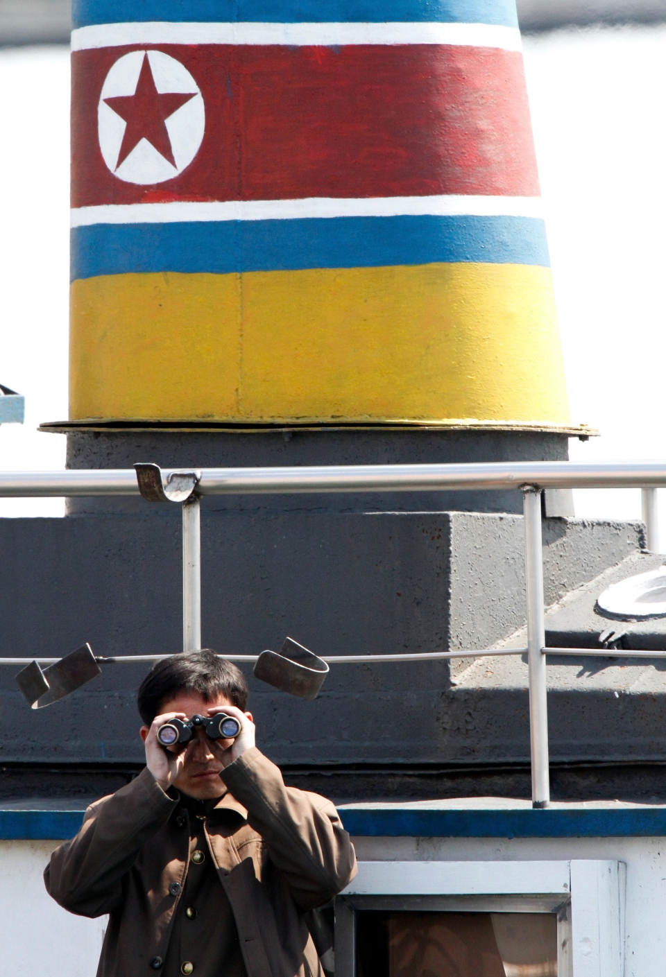 A North Korean soldier uses binocular monitoring on a boat along the river bank of the North Korean town of Sinuiju, opposite to the Chinese border city of Dandong, Wednesday, April 10, 2013. (AP)