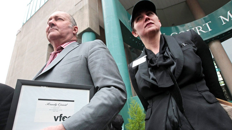 U.S. actor Randy Quaid, left, holds a Vancouver Film Critic's Circle Award he was presented with for the 2009 Canadian film 'Real Time,' as he stands with his wife Evi during a news conference in Vancouver, B.C., on Wednesday February 23, 2011. (Darryl Dyck / THE CANADIAN PRESS)