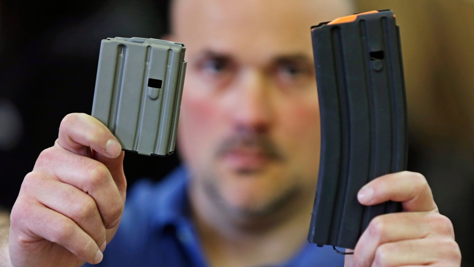 Jonathan Scalise, owner of Ammunition Storage Components, holds up a 10 round, left, and a 30 round, right, magazine that his company manufacturers for the AR-15 rifle in New Britain, Conn., Wednesday, April 10, 2013. (AP / Charles Krupa)