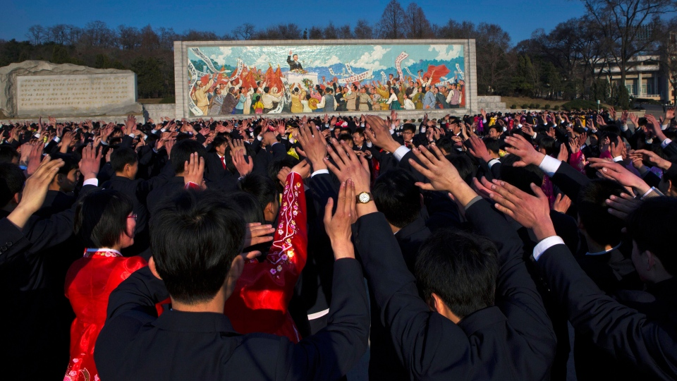 North Koreans dance together beneath a mosaic painting of the late leader Kim Il Sung during a mass folk dancing gathering in Pyongyang on Thursday, April 11, 2013. (AP / David Guttenfelder)