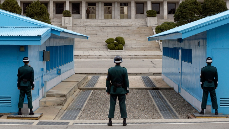 A North Korean soldier, background, looks to the southern side as South Korean soldiers stand guard at the border village of Panmunjom, which has separated the two Koreas since the Korean War, in Paju, north of Seoul, South Korea on Wednesday, April 10, 2013. (AP / Lee Jin-man, File)