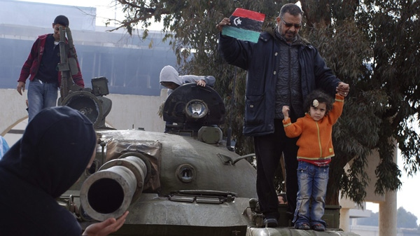 Libyans stand on an army tank at the state security camp in Benghazi, Libya, Tuesday, Feb. 22, 2011. (AP Photo/Alaguri)