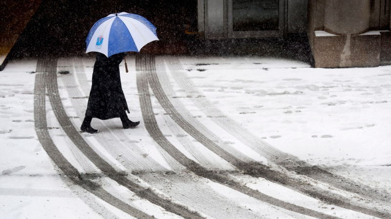 A Montrealer walks during a spring snow storm Friday, April 12, 2013 in Montreal. THE CANADIAN PRESS/Paul Chiasson