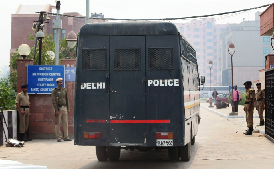 A Delhi state police van believed to be carrying an unknown number of suspects accused of the gang rape and murder of a woman in December, 2012, arrives at the district trial court in New Delhi, India, Monday, March 11, 2013. (AP / Manish Swarup)