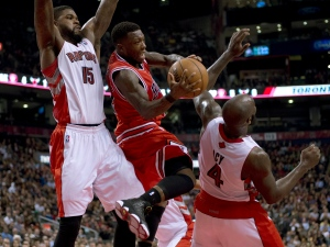 Chicago Bulls guard Nate Robinson (centre) passes off the ball as he runs into Toronto Raptors forwards Amir Johnson (left) and Quincy Acy (right) during first half NBA action in Toronto on Friday April 12, 2013. THE CANADIAN PRESS/Frank Gunn