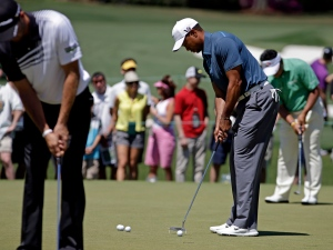 Tiger Woods, right, putts on the practice green before the third round of the Masters golf tournament in Augusta, Ga., on Saturday, April 13, 2013. (AP / Darron Cummings)