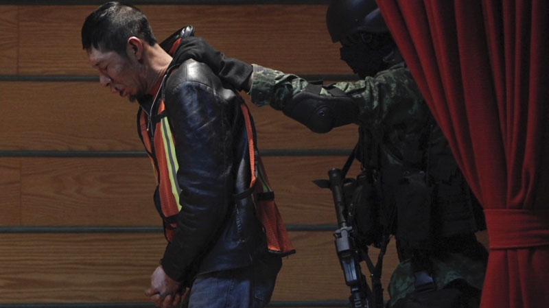 A soldier escorts Jesus Ivan Quezada Pena, an alleged member of the criminal gang led by Julian Zapata Espinoza, not shown, who is the main suspect in the Feb. 15 killing of U.S. Immigration and Customs, ICE, agent Jaime Zapata, during a presentation for the media in Mexico City, Wednesday, Feb. 23, 2011. (AP Photo/Miguel Tovar)