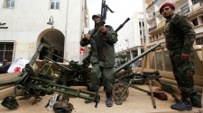 Gunmen prepared to fight against Libyan leader Moammar Gadhafi stand on a small military truck with weapons taken from a Libyan military base, in Benghazi, Libya, on Thursday Feb. 24, 2011. (AP / Hussein Malla)