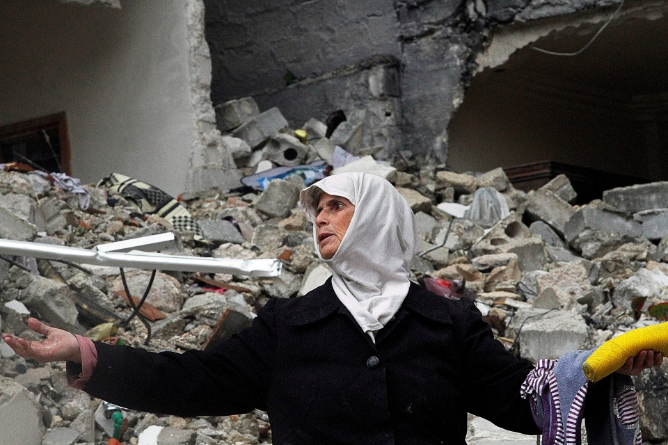 A Syrian woman stands amid the ruins of her house which was destroyed in an airstrike by government warplanes a few days earlier, killing 11 members of her family, in the neighborhood of Ansari, Aleppo, Syria. (AP / Abdullah al-Yassin)