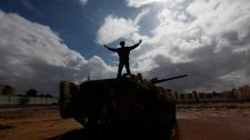 A Libyan man stands over a destroyed tank as he flashes V signet Al-Katiba military base after it fell to anti-Libyan Leader Moammar Gadhafi in Benghazi, Libya, on Thursday Feb. 24, 2011. (AP / Hussein Malla)