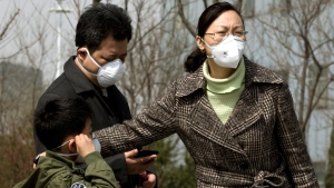 A Chinese family wears face masks near a specialized fever clinic inside the Ditan Hospital, where a Chinese girl was being treated for a strain of bird flu, in Beijing Sunday, April 14, 2013. (AP / Andy Wong)