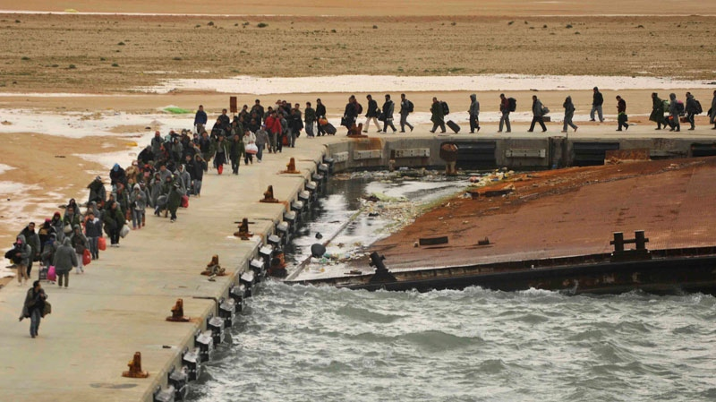 In this photo released by China's Xinhua News Agency, Chinese nationals wait for Greek vessels chartered by the Chinese government, which are pulling in to shore at Benghazi port, Libya, Friday, Feb. 25, 2011.  (AP / Xinhua, Yu Yang)