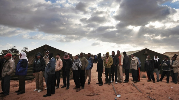 Egyptians who used to work in Libya and fled the unrest in the country, wait for their breakfast in a makeshift refugee camp set up by the Tunisian army at the Libyan border in Ras Ajdir, Tunisia, Friday, Feb. 25, 2011. (AP Photo/Lefteris Pitarakis)