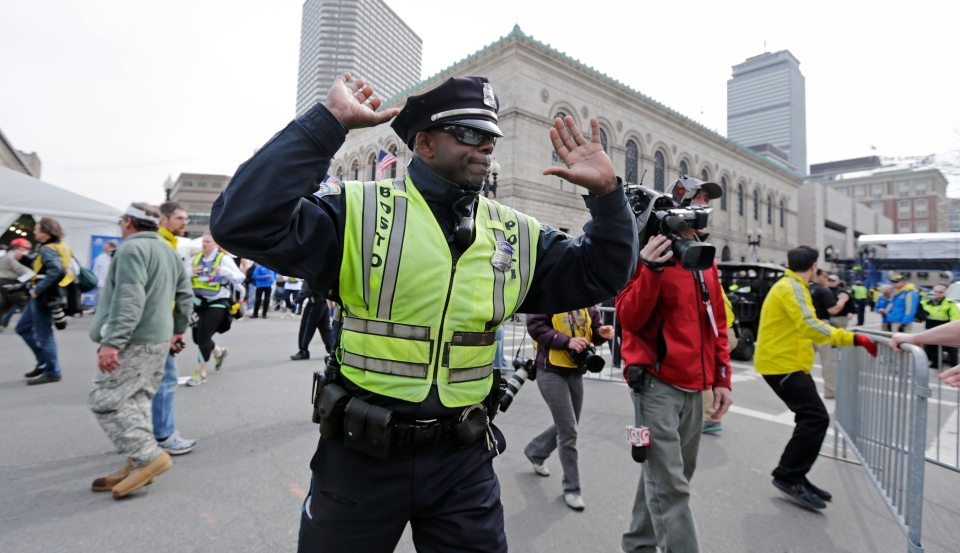 A Boston police officer clears Boylston Street following an explosion at the finish line of the 2013 Boston Marathon in Boston, Monday, April 15, 2013. (AP / Charles Krupa)