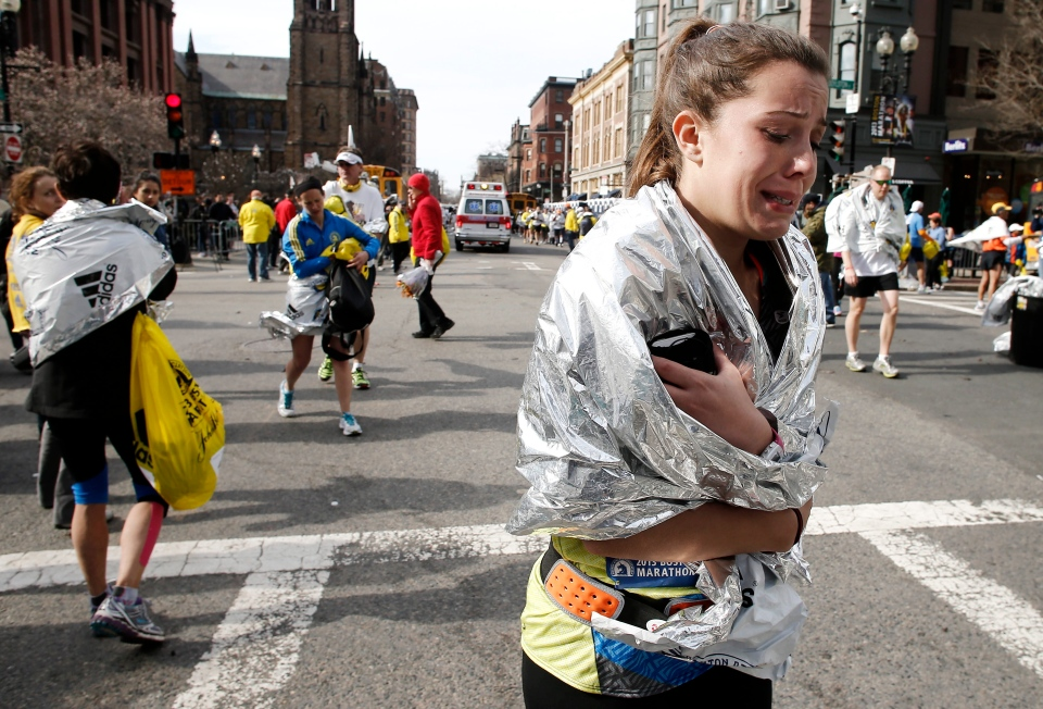 An unidentified Boston Marathon runner leaves the course crying near Copley Square following an explosion in Boston Monday, April 15, 2013. (AP / Winslow Townson)