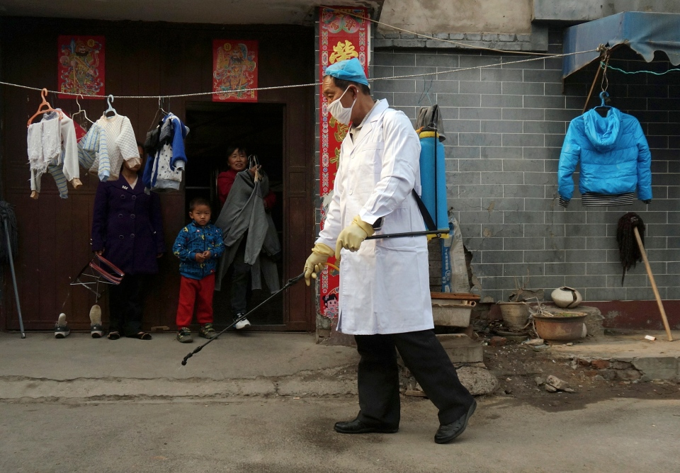 A family watches a worker spray disinfectant in Naidong village, where a boy tested positive for the H7N9 virus, in Beijing Monday, April 15, 2013. (AP)