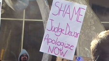A sign calling for an apology from Justice Robert Dewar of Queen's Bench Court for his controversial remarks is shown at a protest at the Manitoba Law Courts in Winnipeg, Friday, Feb. 25, 2011.