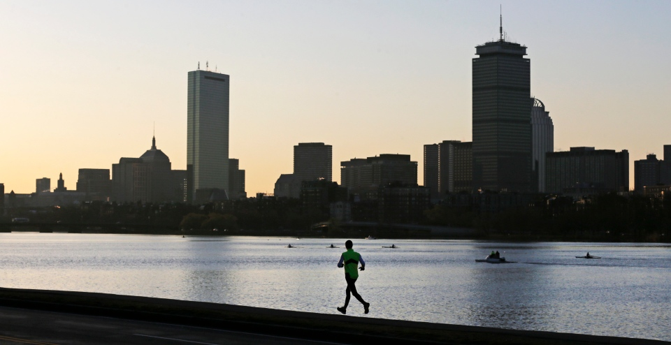 In this file photo a solitary runner heads down the banks of the Charles River in Cambridge, Mass., in front of the Boston skyline. (AP Photo/Charles Krupa)