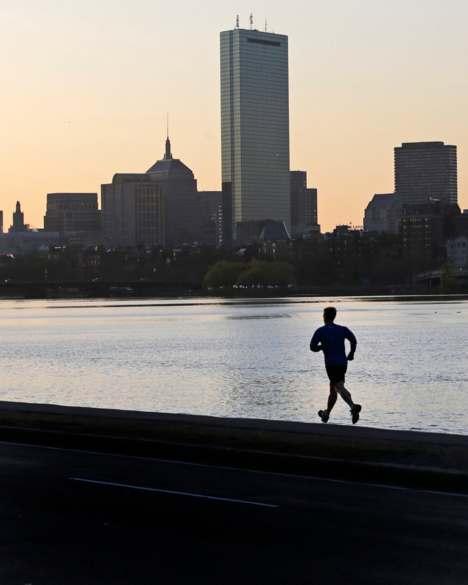 A solitary runner heads down the banks of the Charles River in Cambridge, Mass., in front of the Boston skyline, at dawn the morning after explosions at the Boston Marathon, Tuesday, April 16, 2013. (AP / Charles Krupa)