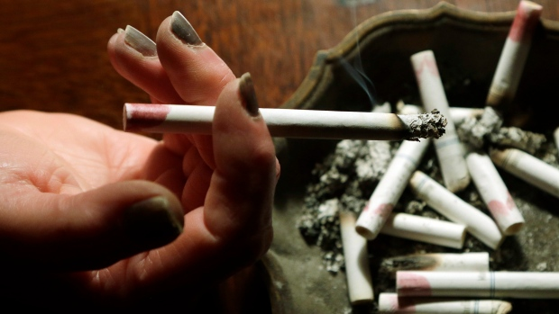 A woman smokes a cigarette at her home in this March 2013 file photo. (AP Photo/Dave Martin)