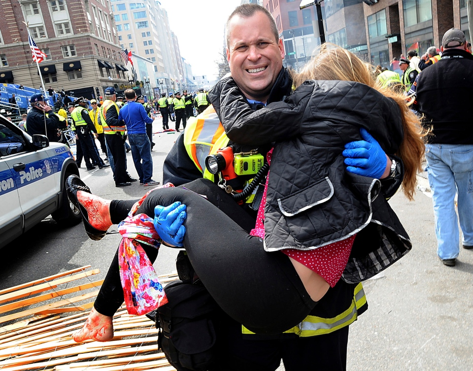 Boston Firefighter James Plourde carries an injured girl away from the scene after a bombing near the finish line of the Boston Marathon on April 15, 2013. (MetroWest Daily News/Ken McGagh)